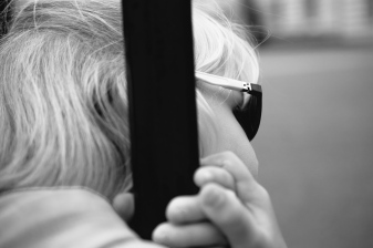 Young girl peering out as she holds on the bar.